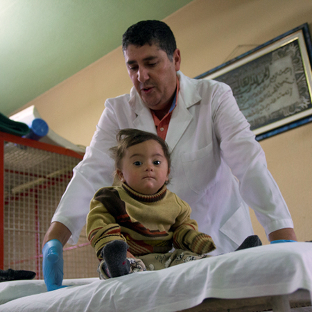 Two-year-old Zainab with a doctor