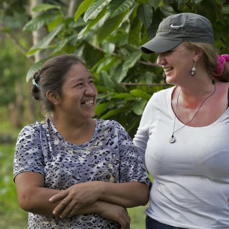 Emma Donlon speaking and laughing with local woman Esther in the Amazon rainforest