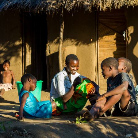 A mother sits with her three children chatting and laughing in Malawi