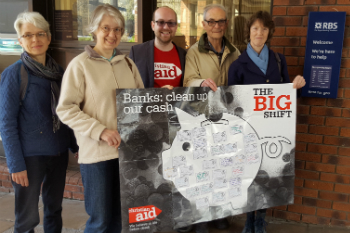 Five campaigners hold a Big Shift poster outside RBS in Exeter