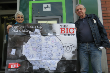 Two campaigners hold a Big Shift poster outside of Lloyds Bank in Manchester