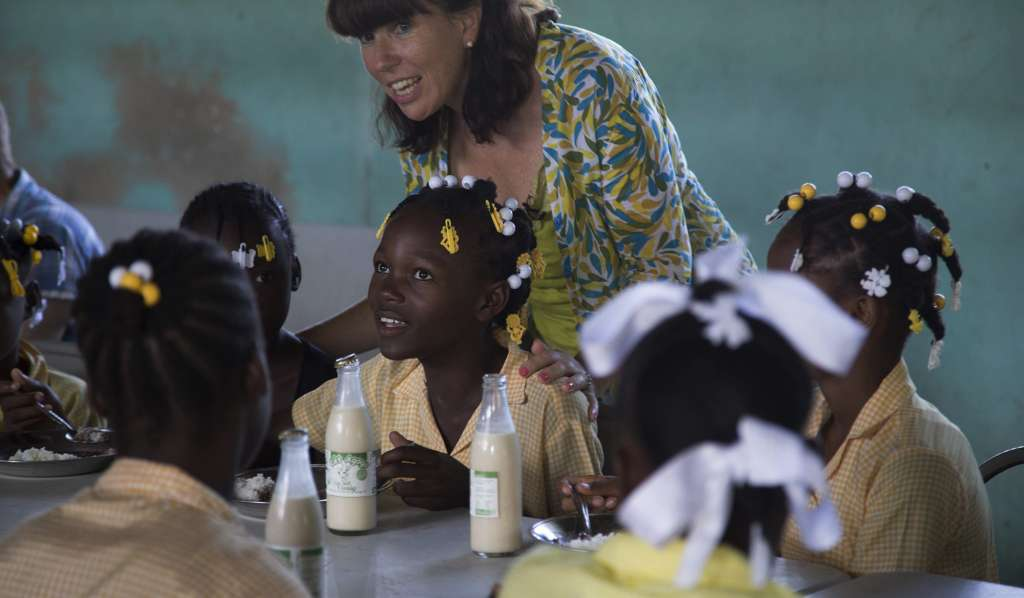 Kathy Childress stands among a group of school children working at their desks in Haiti