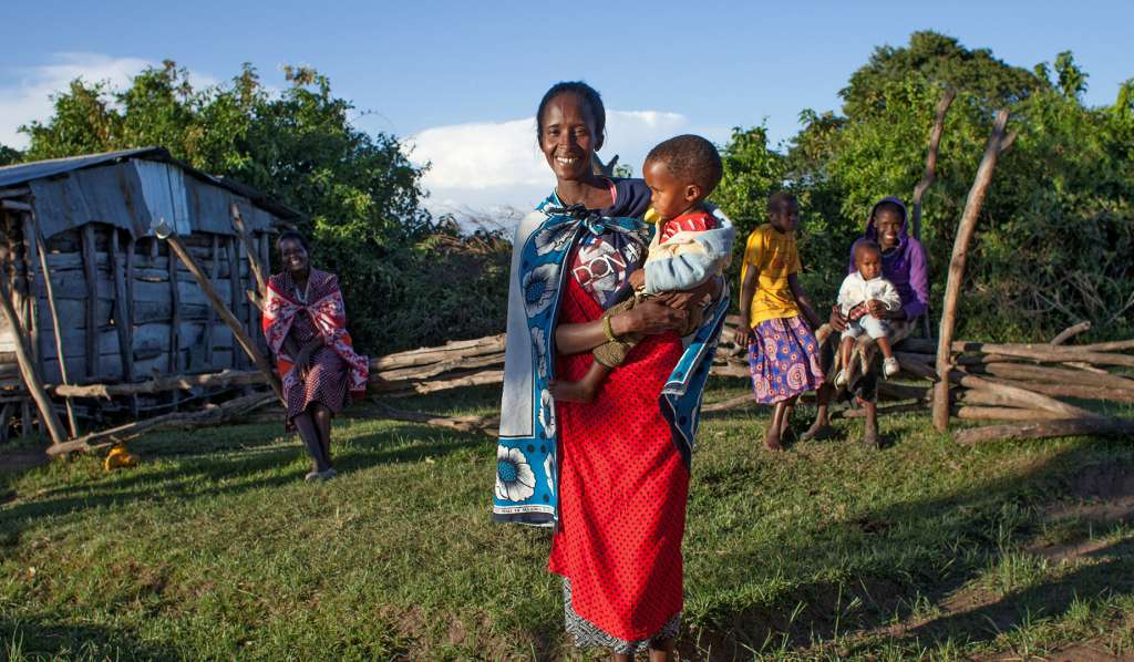 A mother stands in a Maasai village in Kenya, holding her child on her hip
