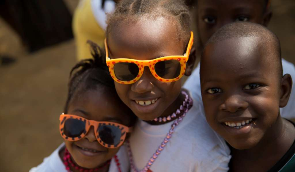 Three children smiling in Sierra Leone