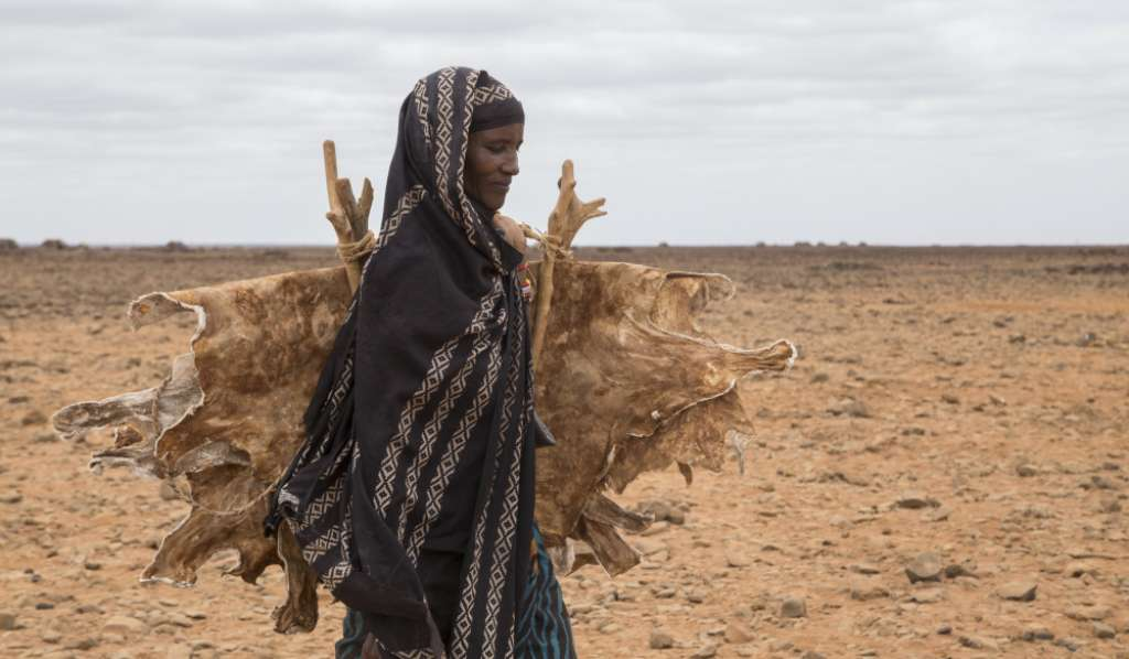 Dimma, a lady living in northern Kenya, walks across dry land.