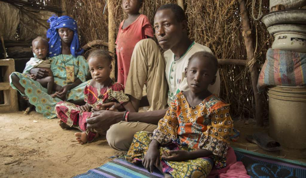 Ibrahim, a man in Kenya, and his family, sitting in their home