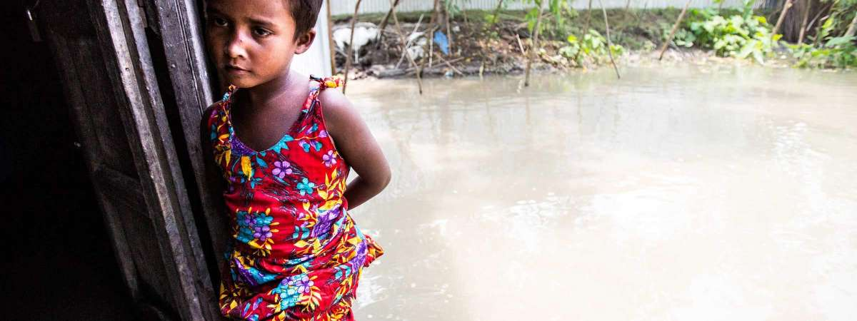 A little girl stands in the doorway of her flooded home in Bangladesh