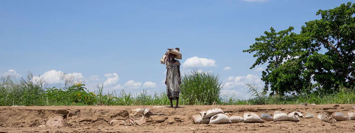 A woman walks across dry land