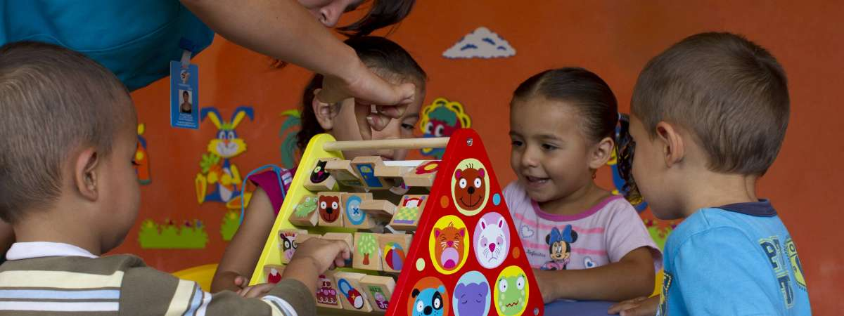Woman and children play with educational toy