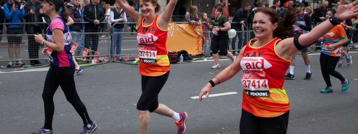 Two female London Marathon runners wave at the crowd
