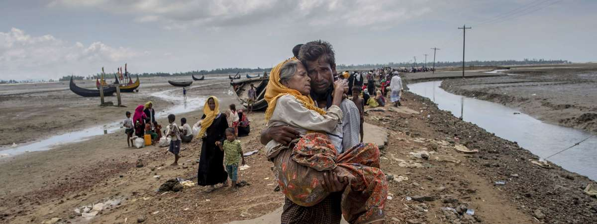 A Rohingya man walks towards a refugee camp carrying his mother after crossing over from Myanmar into Bangladesh.