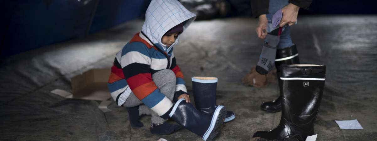 Young Syrian boy puts on a pair of boots