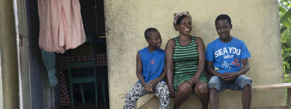 Vilia with her sons outside their Christian Aid built hurricane resistant home
