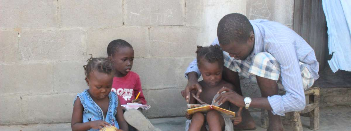 Evaristo looking at books with his children in a doorway in Angola
