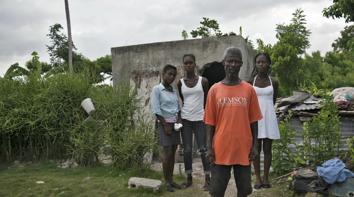 Marcelin and his family stand outside their home in Haiti