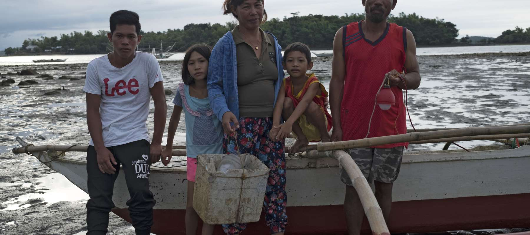 Mary Ann and her family beside their fishing boat