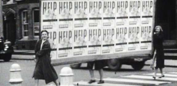 Women cross the road carrying a large banner covered in posters with 'help' written on them.