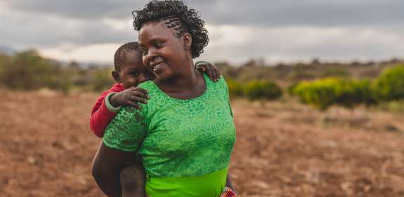 Faith Muvili and her son in a field in Makueni County, Kenya