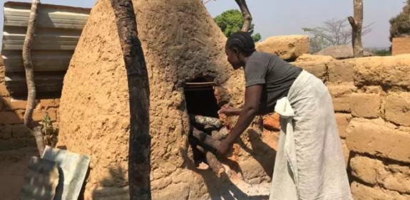 Rosa Domingos tends her clay oven in her village bakery, Angola