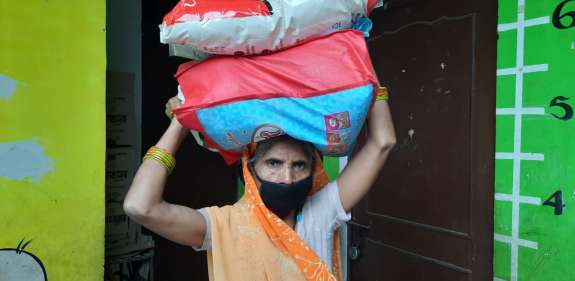 A woman holds one of 200 dry ration packs distributed by partners EFICOR in Dehli to help households cope with loss of income over lockdown.