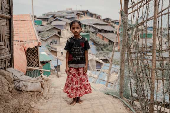Asha stands in a a refugee camp in Bangladesh