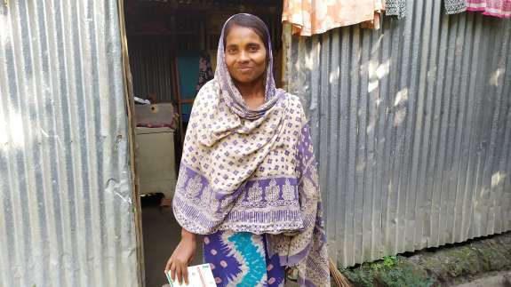 Morjina Begum standing outside her home in Basedpur village.