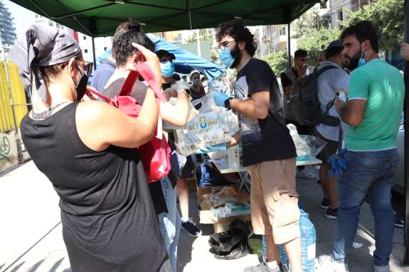 Caption: Christian Aid's local partner Basmeh & Zeitooneh hands out food and water to people in some of the areas most affected by the Beirut blast while wearing masks and gloves to help keep safe