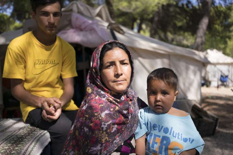Nejebar a refugee from Afghanistan sits in a Greek camp with her sons
