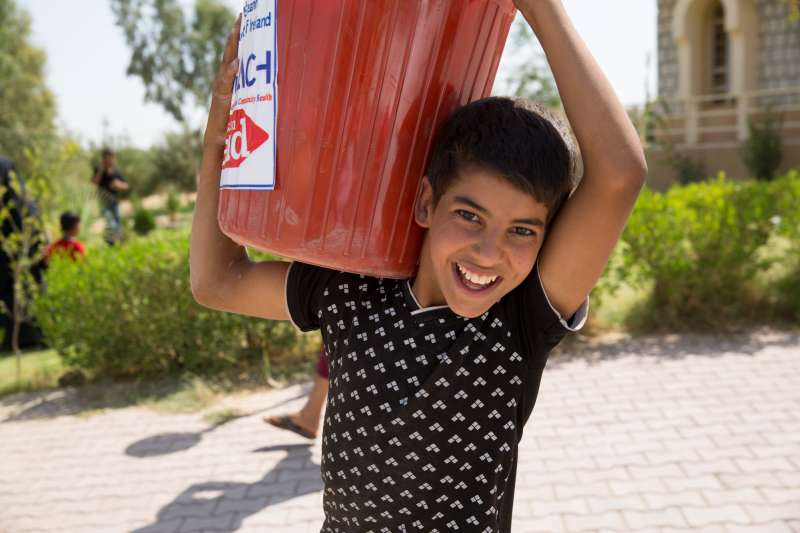 A boy carries a Christian Aid bucket in Iraq