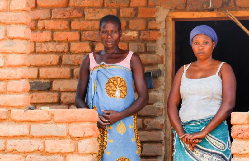 Ruth and her mother in Malawi, standing in their brick house