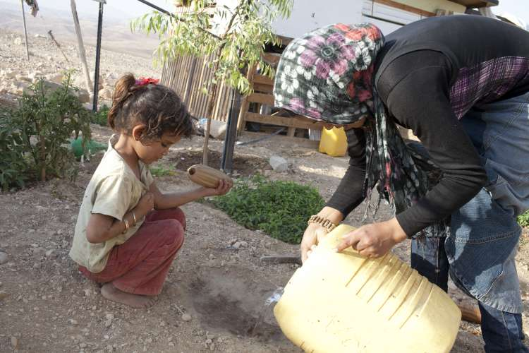 A young girl and her sister planting gourd seeds in the West  Bank in a project supported by Christian Aid