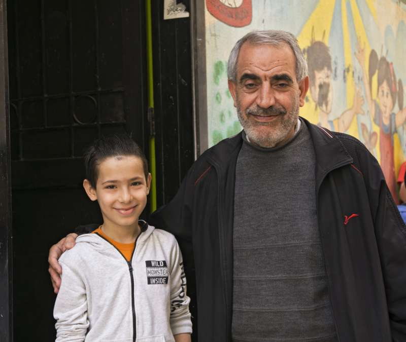 Hassan and his granddad outside the children's centre, where he's found some security.