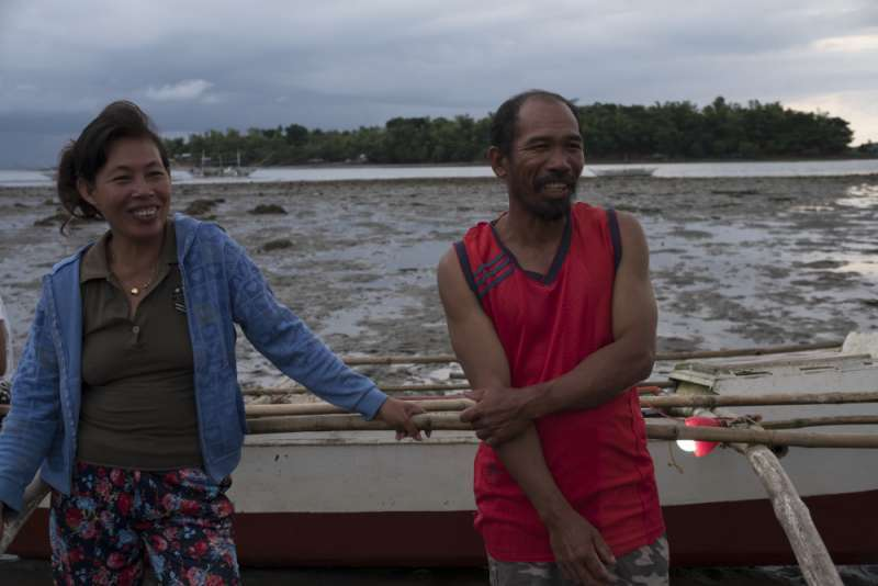 Mary Ann and Jose by their fishing boat, equipped with solar light.