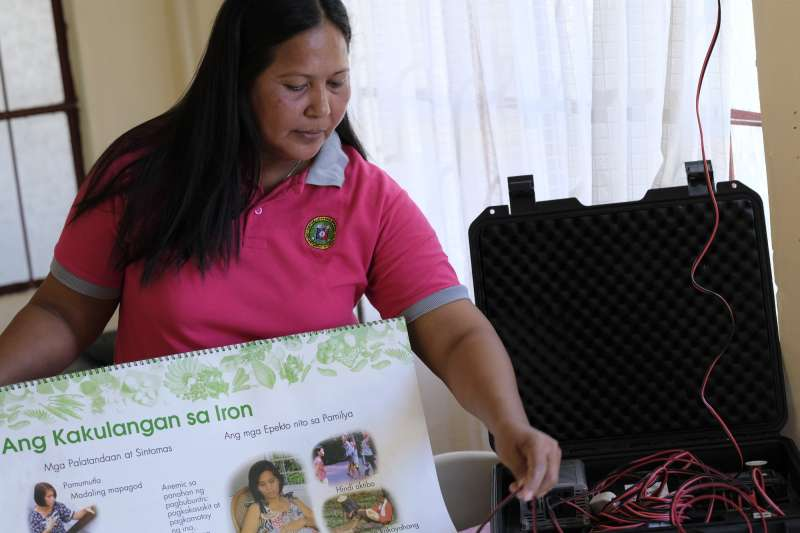 43-year-old health worker Amalyn is pictured in the island's local health centre with the portable solar charger.