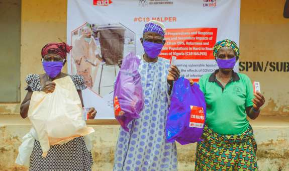 Community in Nigeria holding Covid19 protection packs from Christian Aid