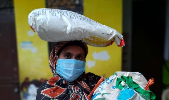 A woman holds one of 200 dry ration packs distributed by partners EFICOR in Dehli in 2020 to help households cope with loss of income over lockdown.