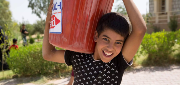 A young boy carries a bucket on his shoulder as part of a Christian Aid emergency response