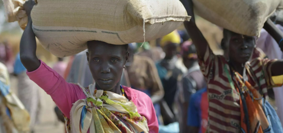 A displaced woman carries a bag of grain in South Sudan