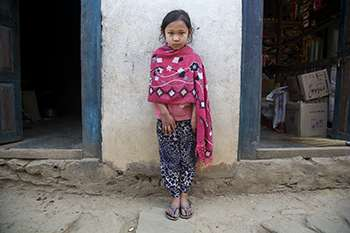 A young Nepalese girl stands against a wall between two doorways