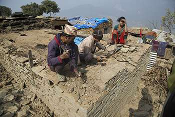 Two men and a woman rebuilding in Nepal
