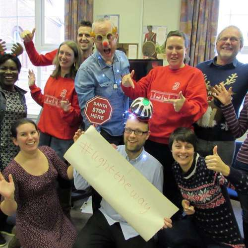 Christian Aid East Midlands team holding a 'Light the Way' banner