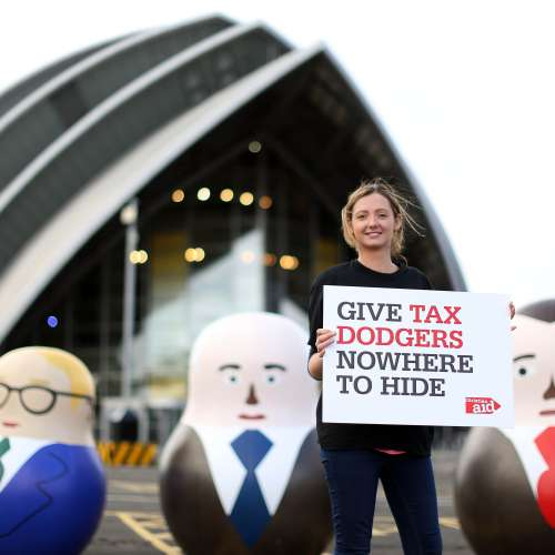 A Christian Aid supporter holds a placard which reads 'give tax dodgers nowhere to hide' in front of three businessmen Russian dolls.