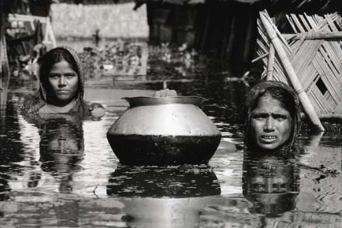 Mother and daughter in the flooded street outside their home in Dhaka, Bangladesh, September 1998