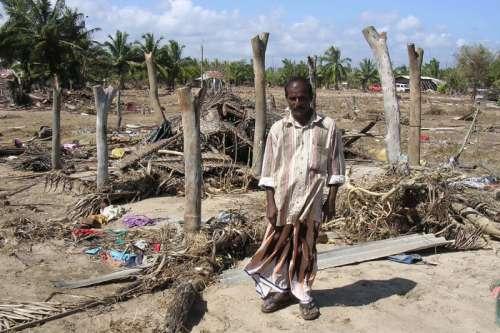 Man standing in beach strewn with clothing and remains of destroyed buildings
