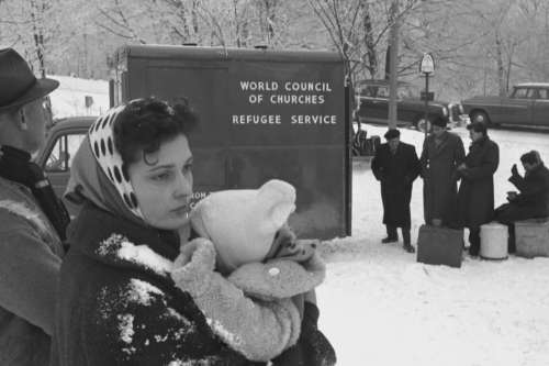 Woman holding baby in front of World Council of Churches refugee service van.