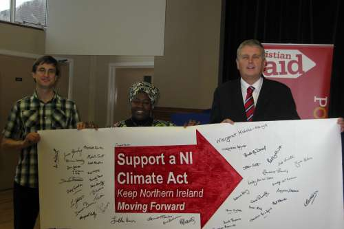 Jim Wells is presented with a banner by Christian Aid supporters at a Bearing Witness event in Comber