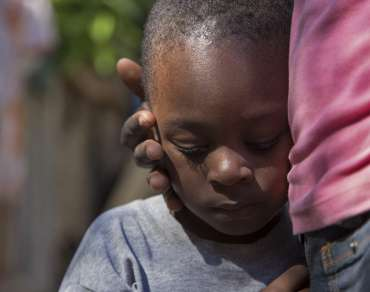 Young boy resting his head against his mother in Ganthier village