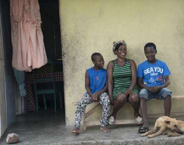 Vilia and her sons outside their hurricane resistant home in Haiti