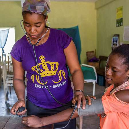 A community health nurse uses a stethoscope to examine a young woman.