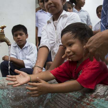 Children in Bolivia holding their hands under a running water tap